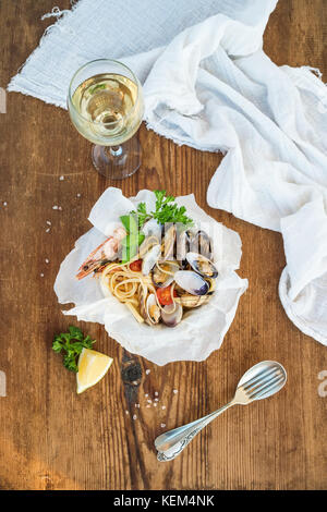 Meeresfrüchte Pasta Spaghetti mit Muscheln und Krabben in der Schale, Glas Weißwein über rustikale Holz Hintergrund - Stockfoto