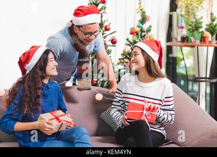 Weihnachtsfeier mit Freunden, Asien Menschen Geschenk Austausch mit lächelndes Gesicht, Urlaub feier Konzept - Stockfoto