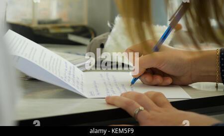 Nahaufnahme eines weiblichen Hand schreiben auf ein leeres Notebook mit einem Stift. close-up für eine weibliche - Stockfoto