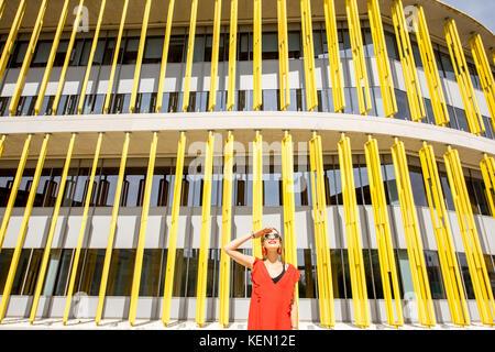 Frau auf dem gelben Gebäude Hintergrund - Stockfoto