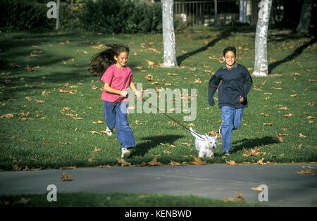 Kindheit Jugendliche person Junge Mädchen laufen Park Leine sorglos gemächlich Freiheit freudigen Hund freudig Genießen - Stockfoto