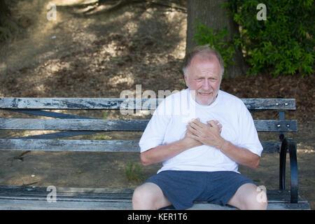 Closeup Portrait, alte Mann umklammert, in Herz Schmerz in der Brust, auf der Bank sitzen, isoliert im Freien, grünen - Stockfoto