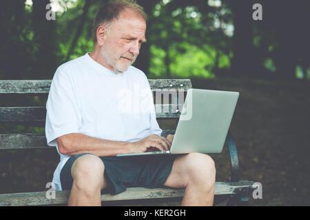 Closeup Portrait, Senior reifer Mann im weißen Hemd weg, Browsing digitalen Computer Laptop, isolierte Hintergrund - Stockfoto