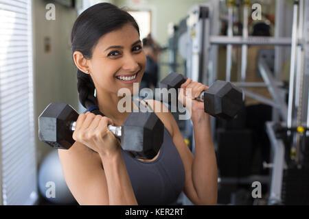 Closeup Porträt, junge attraktive Frau heben Gewicht in der Turnhalle, im Innenbereich mit Ausrüstung im Hintergrund - Stockfoto