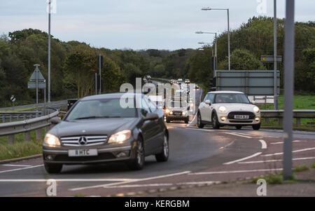 Autos mit Licht am Verkehr gefahren werden in den frühen Morgen rush-hour, auf der A27 Straße in Großbritannien. - Stockfoto