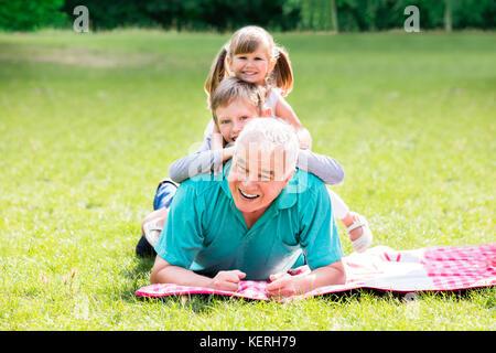Portrait von Happy Family Spaß auf grünem Gras zusammen liegen im Park - Stockfoto