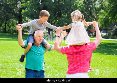 Gerne alten Großeltern genießen Spaß piggyback Ride mit Enkelkindern zusammen in Park - Stockfoto