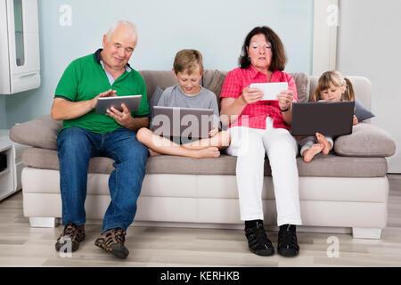 Familie mit Kindern sitzen auf der Couch mit Laptops und Tablet-pcs zu Hause - Stockfoto