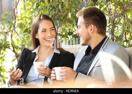 Zwei glückliche Führungskräfte im Gespräch in der Kaffeepause in einer Bar auf der Terrasse sitzen - Stockfoto