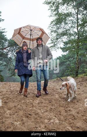 Junge trendige Paar, männlichen & weiblichen tragen Winter Kleidung und Unterschlupf unter einem Regenschirm Spaziergang - Stockfoto