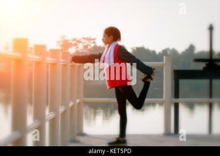 Blurry der athletische Frau Asien Aufwärmen und junge Athletin auf einem Training und Stretching in einem Park vor - Stockfoto