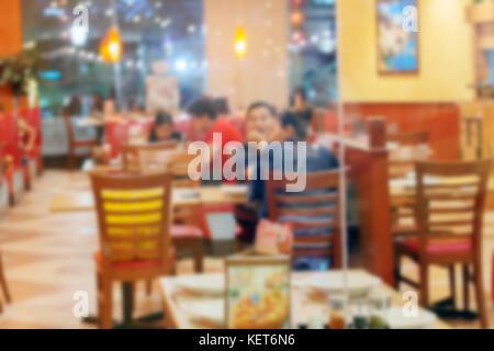 Unschärfe der Leute genießen, Essen und Sprechen in einem Restaurant. - Stockfoto