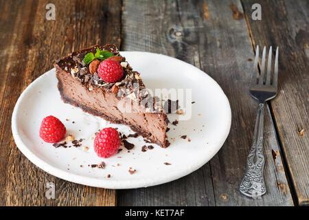 Schokolade Käsekuchen oder ein Stück Schokolade Torte mit Himbeeren und zerkleinert Nüsse auf weiße Platte eingerichtet. - Stockfoto