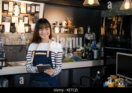 Portrait von lächelnden asiatischer barista Holding digital Tablet am Zähler in Coffee Shop. Cafe Restaurant Service, - Stockfoto