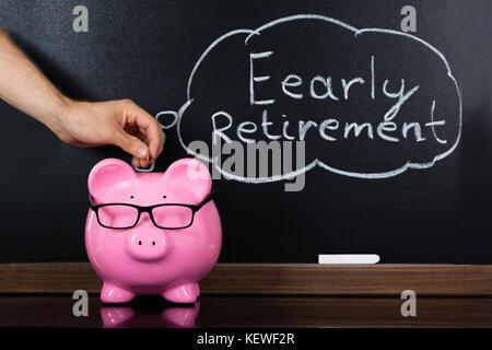 Person Hand einfügen Münze in sparschwein Übersicht Ruhestand Konzept auf der Tafel - Stockfoto