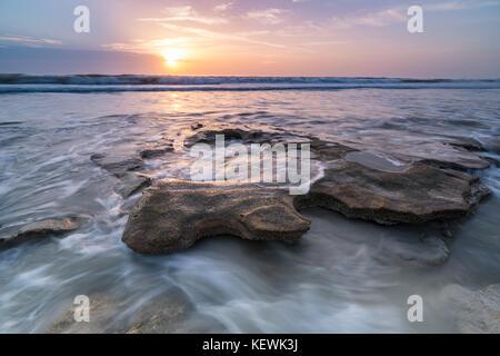 Sonnenaufgang über der Flut Zusammenhaengen ein coquina Rock bei Marineland Beach, Florida - Stockfoto