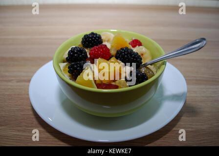 Obst und Beeren Salat (Orangen, Brombeeren, Himbeeren, Bananen) in einer grünen Teller. - Stockfoto