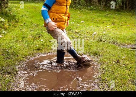 Junge Spaß Spritzwasser in schlammigen Pfützen - Stockfoto