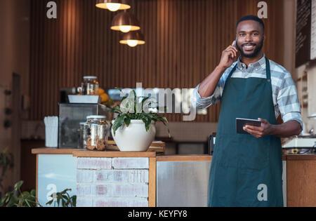 Lächelnd afrikanische Unternehmer sprechen über ein Handy in seinem Cafe - Stockfoto
