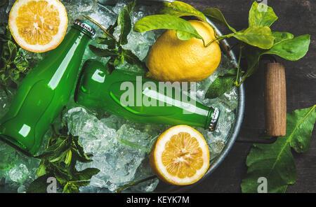 Flaschen grüne Limonade auf abgeplatzte Eis in Metall Fach - Stockfoto