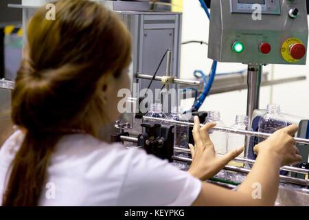 Unidentify asiatische Frau die neue leere Plastikflasche im Wasser Produktionslinie Maschine im Trinkwasser Fabrik. - Stockfoto