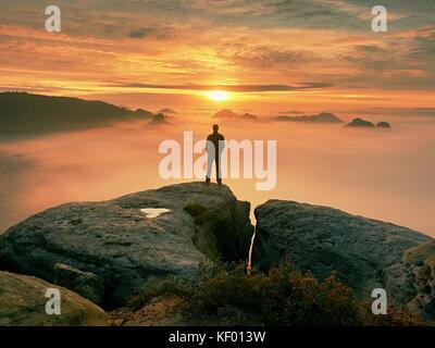 Man steht allein an der Spitze der Rock. Wanderer beobachten, Herbst Sonne am Horizont. schöner Moment das Wunder - Stockfoto