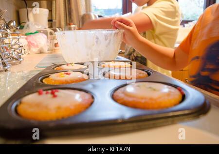 Ein paar der jungen Brüder frisch gebackene Cupcakes mit Zuckerglasur verzieren und Streuseln. - Stockfoto