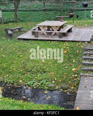 Holztisch und Stühlen für Grillpartys sind im Herbst Ahorn Wald in der Nähe von einem kalten Bach gelegen - Stockfoto