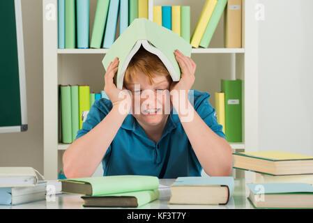 Wütend Junge in Bibliothek holding Buch auf dem Kopf sitzen - Stockfoto