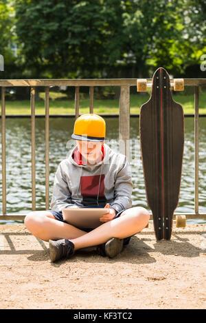 Junge tragen Sie die Kappe mit digitalen Tablet vor Geländer - Stockfoto