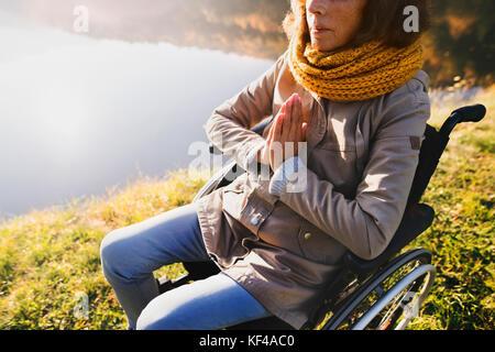 Ältere Frau in einem Rollstuhl im Herbst Natur. - Stockfoto