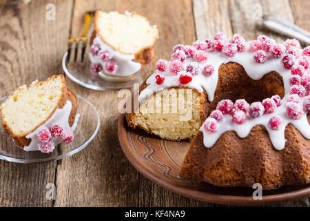 Kandierte Preiselbeeren bundt Cake mit Zitrone Zucker Glasur auf Holzbrett. hausgemachte Herbst und Winter gemütliches - Stockfoto