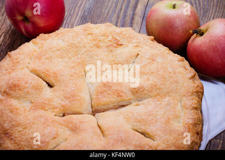 Hausgemachte, traditionelle Herbst Apfelkuchen mit eine flockige Tortenboden auf rustikalen Holztisch