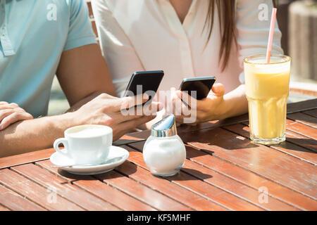 In der Nähe der Jugendlichen glückliches Paar sitzt auf der Bank mit Handy - Stockfoto