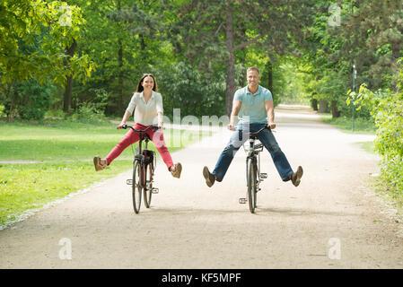 Junge glückliches Paar Reiten Fahrrad im Park am Morgen - Stockfoto