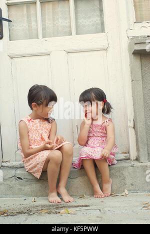 Zwei kleine Mädchen (Schwestern) sitzt auf der Treppe außerhalb eines Hauses und lustig sprechen. Sommer, Retro - Stockfoto
