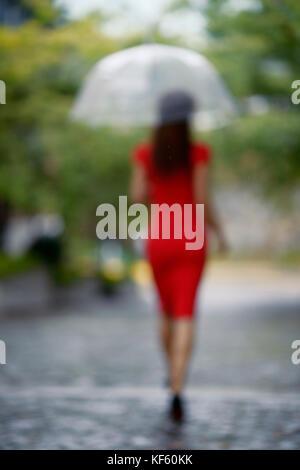 Aus Fokus Portrait von einer Frau im roten elegantes Kleid mit einem Regenschirm zu Fuß im Regen auf einer gepflasterten - Stockfoto