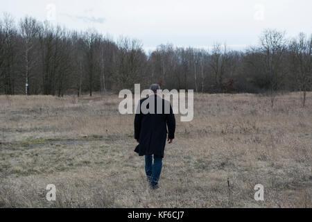 Volle Länge Rückansicht ein Mann mit einem Mantel wandern in einem Feld - Stockfoto