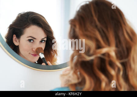 Junge Frau ihre Nase pudern - Stockfoto