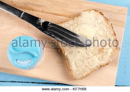 Flach Butter auf Brot mit Messer und auf einem Holzbrett serviert. - Stockfoto