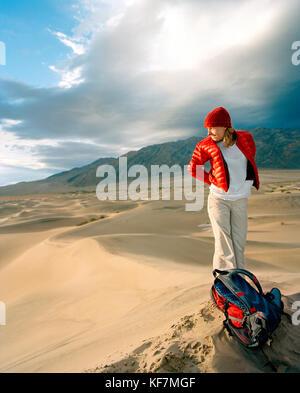 Usa, Kalifornien, junge Frau, die auf Sand dune, Stovepipe Wells, Death Valley National Park - Stockfoto