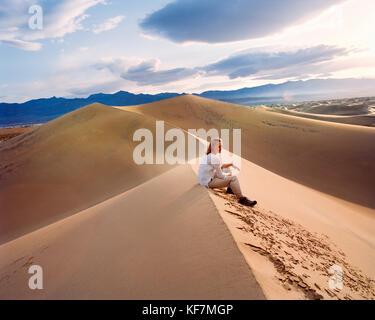 Usa, Kalifornien, junge Frau sitzt auf der Sanddüne, Stovepipe Wells, Death Valley National Park - Stockfoto
