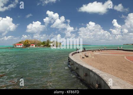 Mauritius, Fischer auf einem Stein Pier in Pattaya an der Wasserfront, Ile mouchoire Rouge in der Ferne - Stockfoto