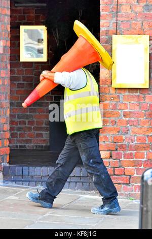 Mann bei der Arbeit entlang Plasterung in Liverpool tragen hohe Sichtbarkeit Jacke mit einem großen leitkegel Poller - Stockfoto