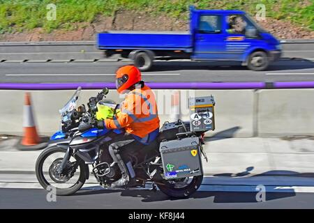 Nahaufnahme von Triumph Motorrad fahrer entlang Lane drei der britischen Autobahn tragen hohe vis Jacke und Helm - Stockfoto