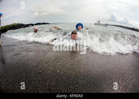 Galapagos, Ecuador, junge Kinder spielen im Wasser von Urbina Bay, die Westseite der Insel Isabela an der Basis - Stockfoto