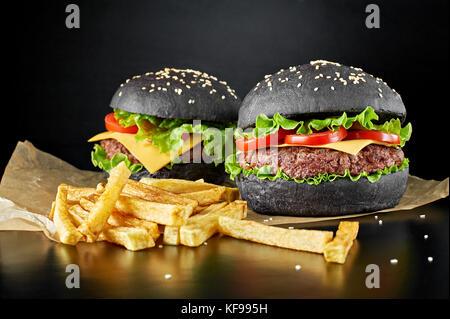 Zwei schwarze Burger mit Pommes frites auf schwarzem Hintergrund isoliert. - Stockfoto