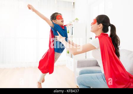 Hübsche junge Mutter Holding süsse kleine Mädchen, Fliegen posing und Spielen als Superheld zu Hause. - Stockfoto