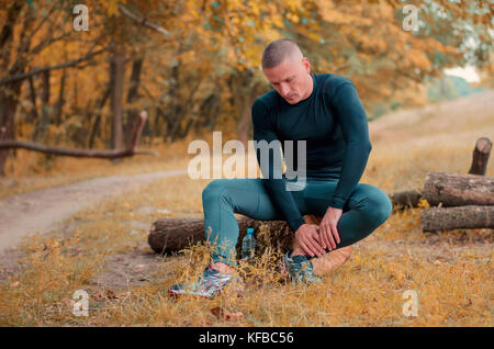 Junge Sportliche Läufer in einem schwarzen Sport T-Shirt, Leggings und Sneakers sitzt auf einem Betrieb einen Knöchel - Stockfoto