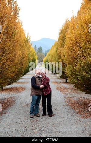 Usa, Oregon, Medford, cal und Judy Schmidt stand unter den Bäumen auf der Farm, Familie Schmidt Weinberge befindet - Stockfoto